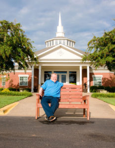 Photo: Jimmy Breckenridge sitting on a bench in front of the BVT chapel